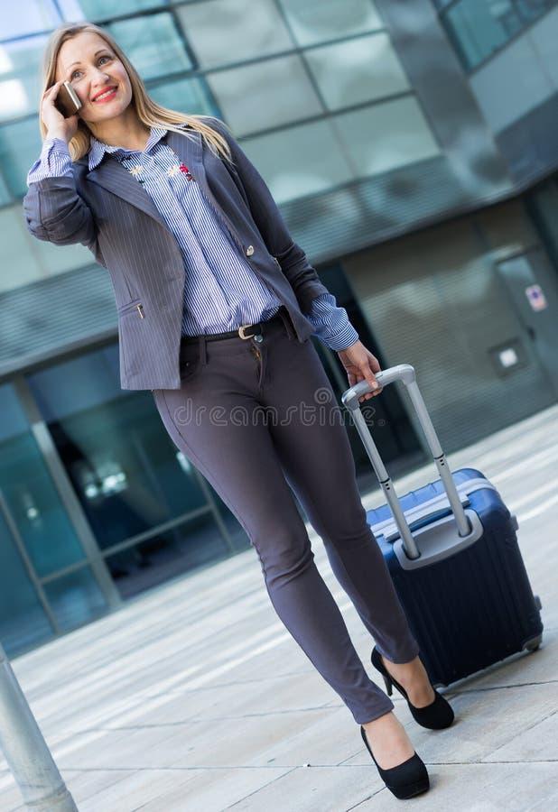 Vrouw in kostuum die zich met bagage en sprekende telefoon bevinden royalty-vrije stock afbeeldingen