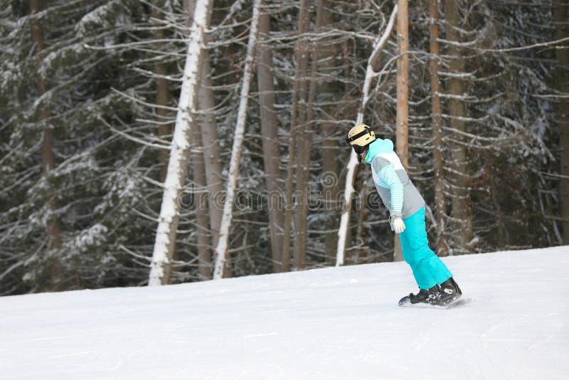 Vrouw in kostuum het snowboarding op heuvel, ruimte voor tekst royalty-vrije stock afbeelding
