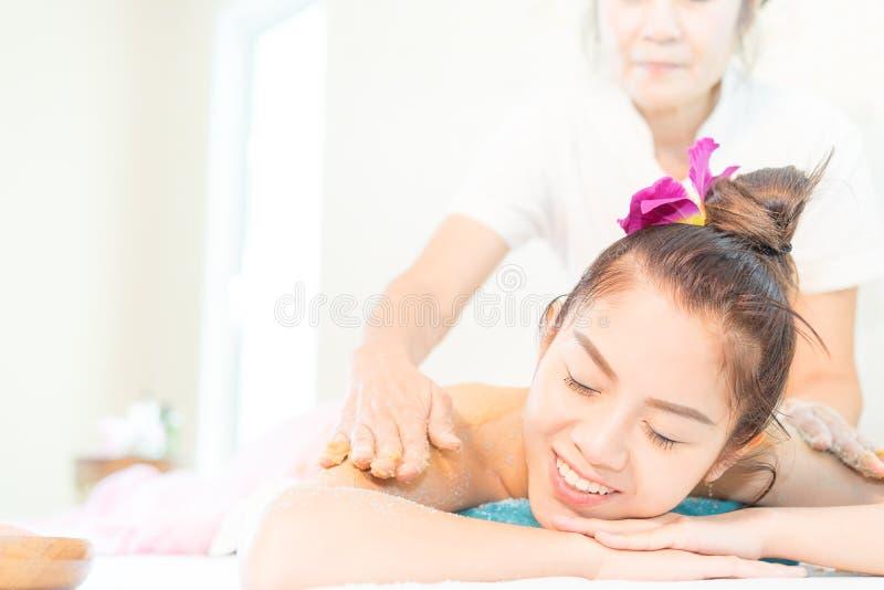 Vrouw in Kuuroord met glimlach terwijl het terugnemen van massage door Kuuroordtherapeut stock foto's