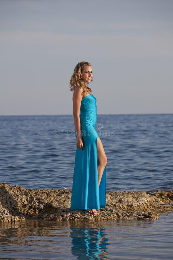 Vrouw in lange kleding op steenachtig strand royalty-vrije stock afbeelding