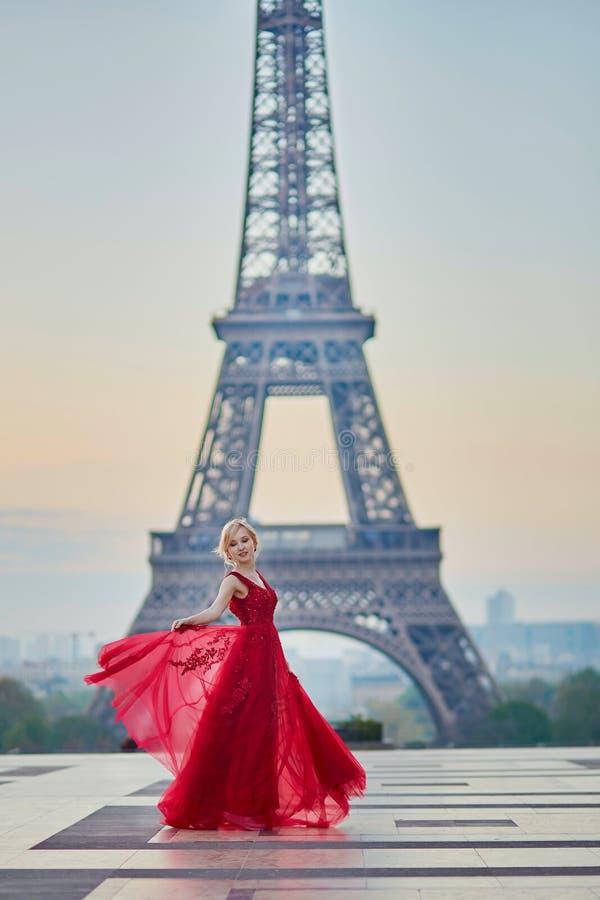 Vrouw in lange rode kleding die dichtbij de toren van Eiffel in Parijs, Frankrijk dansen stock afbeelding