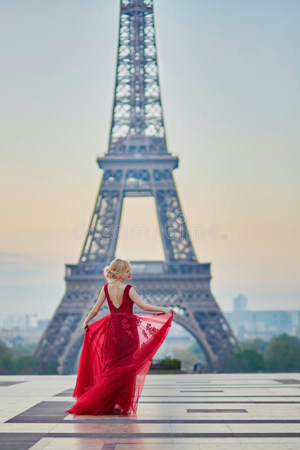 Vrouw in lange rode kleding die dichtbij de toren van Eiffel in Parijs, Frankrijk dansen royalty-vrije stock afbeeldingen