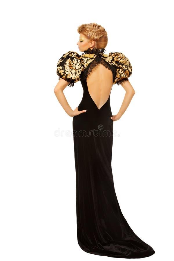 Vrouw in lange zwarte manierkleding met naakt terug over witte bac stock afbeelding