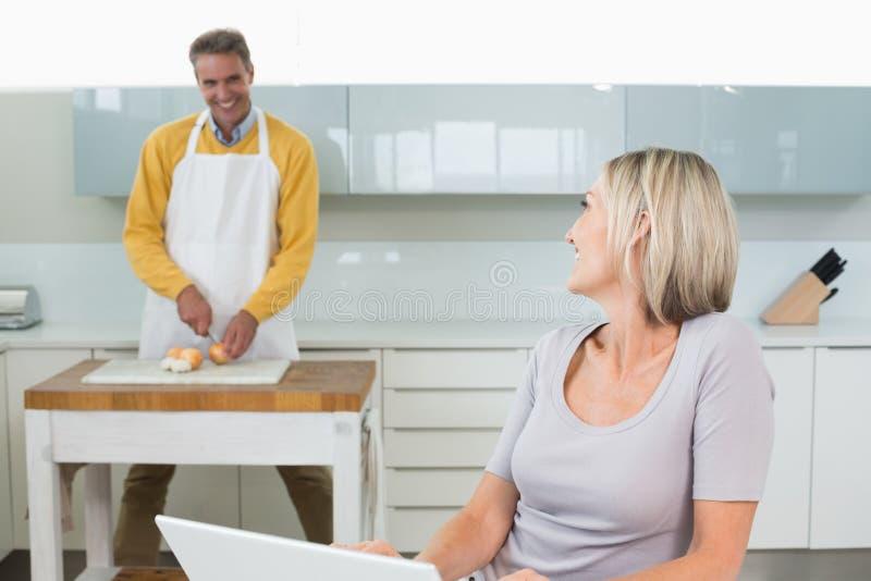Vrouw laptop met behulp van en man die hakkende groenten stock foto's