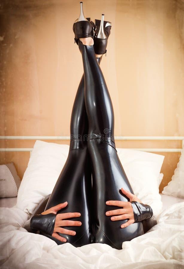 Vrouw in latex in bed royalty-vrije stock afbeeldingen