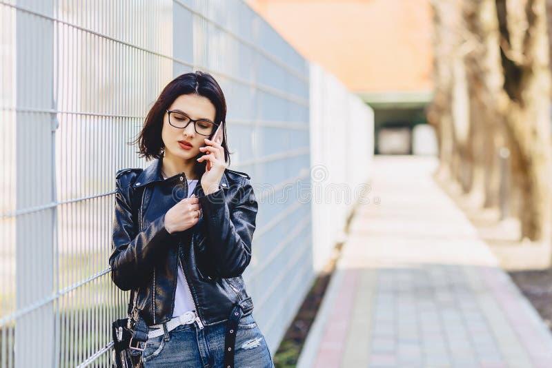 Vrouw in leerjasje in glazen die op telefoon en glimlachen spreken stock afbeelding