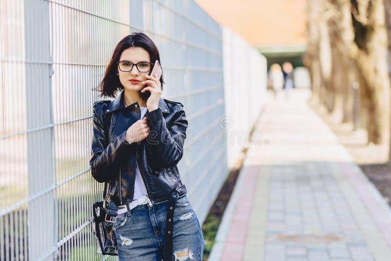 Vrouw in leerjasje in glazen die op telefoon spreken stock afbeeldingen