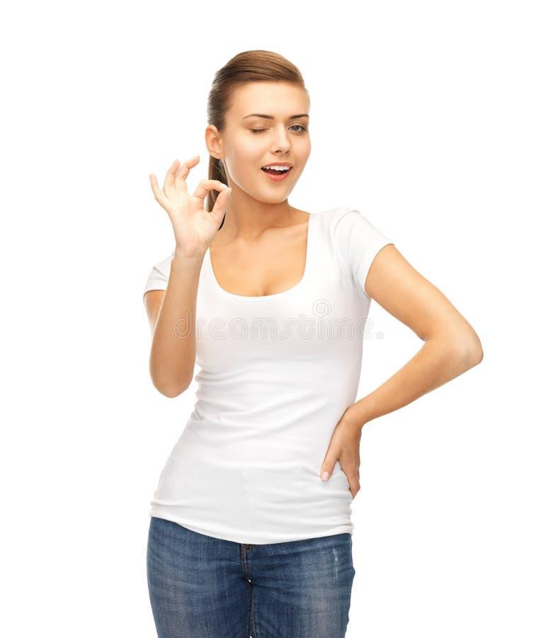 Vrouw in lege witte t-shirt die o.k. gebaar tonen royalty-vrije stock foto