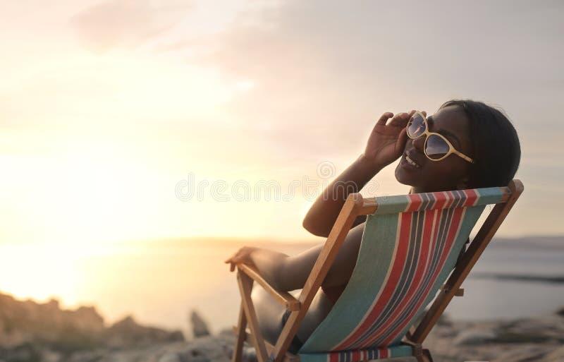 Vrouw in ligstoel royalty-vrije stock afbeelding