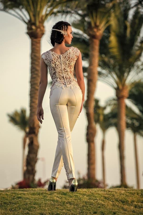 Vrouw of meisje in kant hoogste en witte broek die zich op groen gras bevinden royalty-vrije stock fotografie