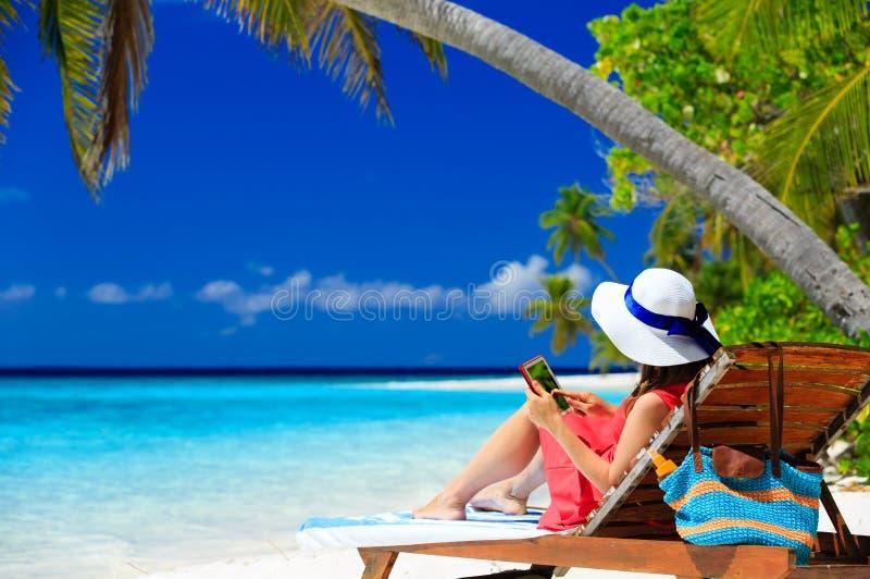 Vrouw met aanrakingsstootkussen op tropisch strand royalty-vrije stock foto