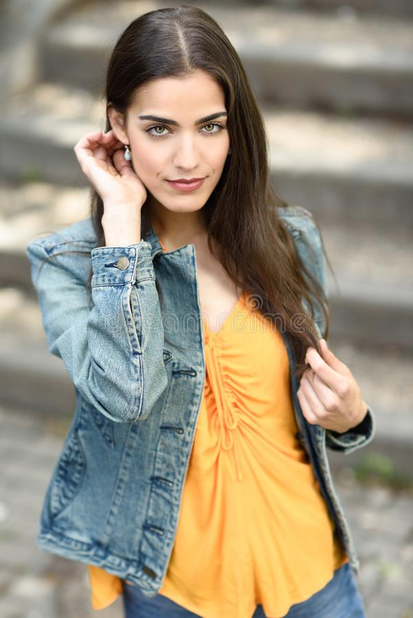 Vrouw met aardig haar die vrijetijdskleding op stedelijke achtergrond dragen stock foto's