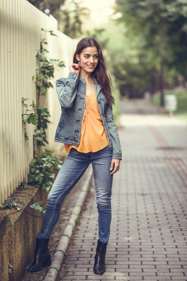 Vrouw met aardig haar die vrijetijdskleding op stedelijke achtergrond dragen stock fotografie