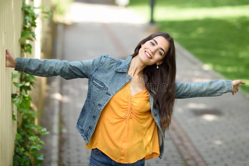 Vrouw met aardig haar die vrijetijdskleding op stedelijke achtergrond dragen stock afbeeldingen