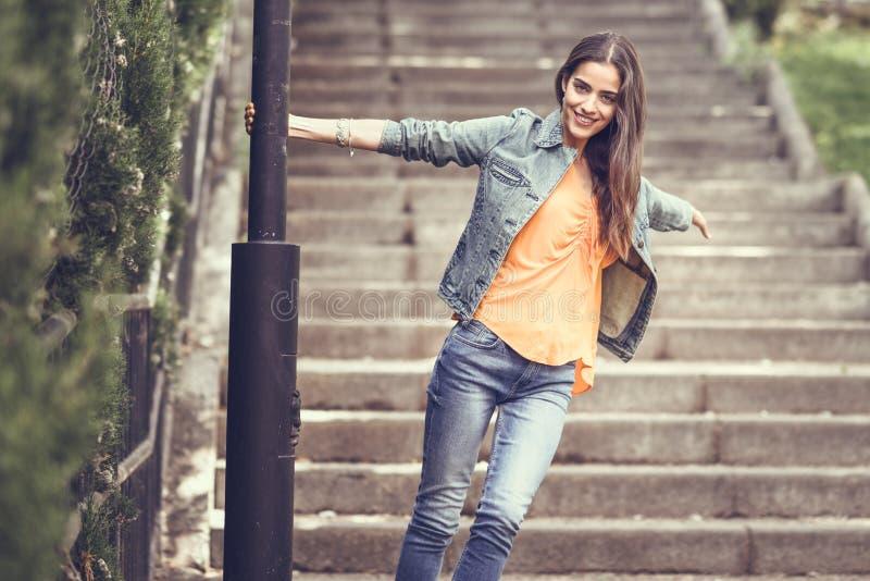 Vrouw met aardig haar die vrijetijdskleding op stedelijke achtergrond dragen royalty-vrije stock afbeeldingen