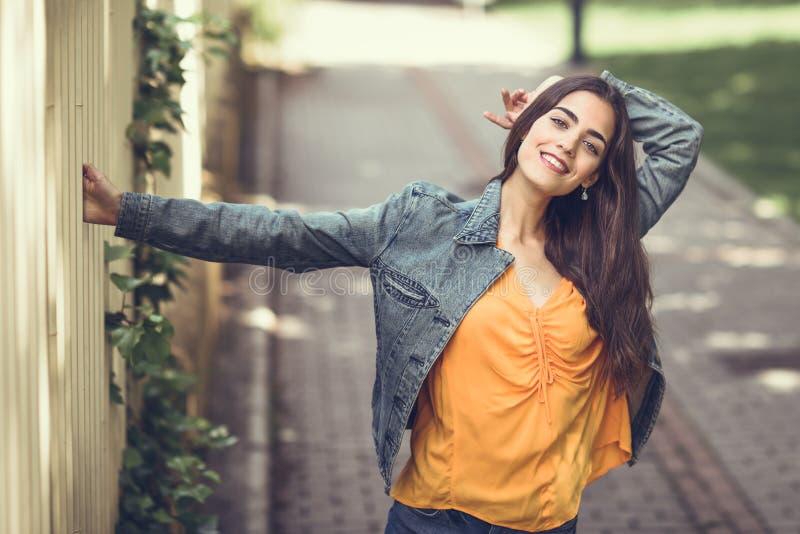 Vrouw met aardig haar die vrijetijdskleding op stedelijke achtergrond dragen royalty-vrije stock foto's