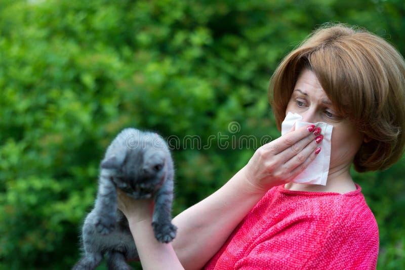 vrouw met allergieën voor een kat stock afbeelding