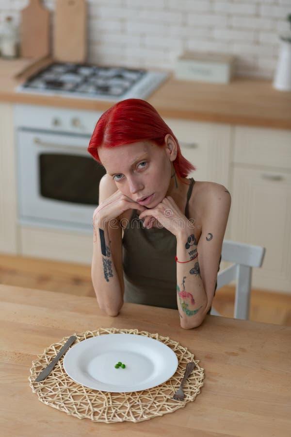 Vrouw met anorexiezitting in de keuken die slecht voelen stock fotografie
