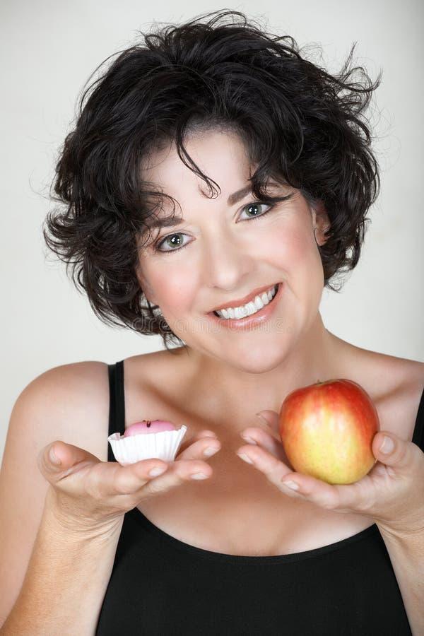 Vrouw met appel en een cake stock afbeelding