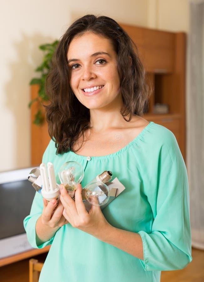 Vrouw met armvol lightbulbs stock fotografie
