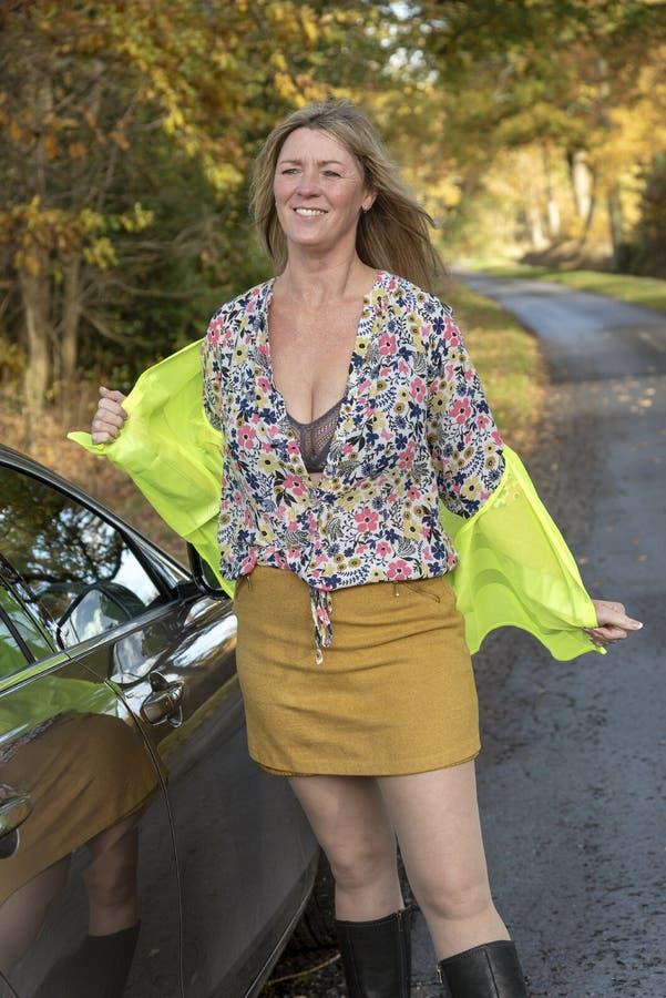 Vrouw met auto en het dragen van een veiligheids weerspiegelend jasje stock foto