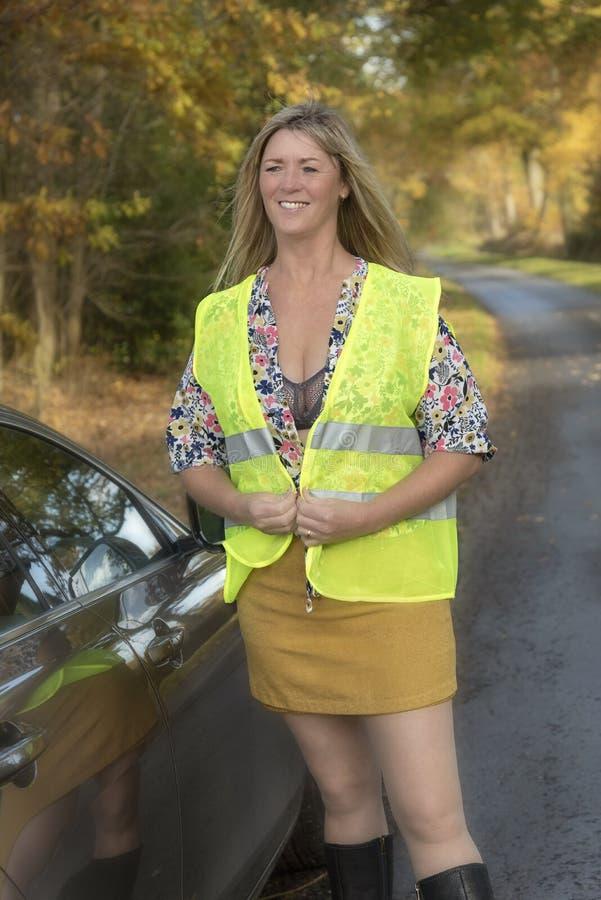 Vrouw met auto en het dragen van een veiligheids weerspiegelend jasje stock afbeeldingen