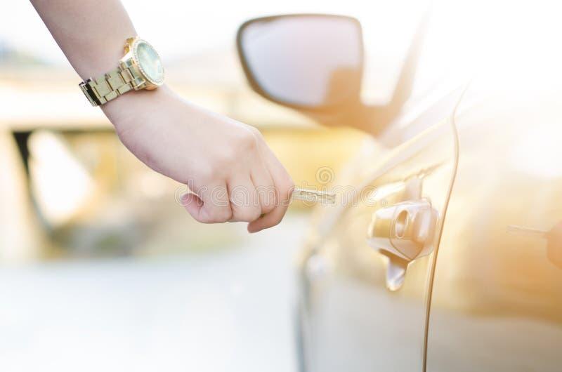 Vrouw met autosleutel Openingsautodeur De hand die van Womaneen deur op een auto openen zonlicht vervoer royalty-vrije stock foto's