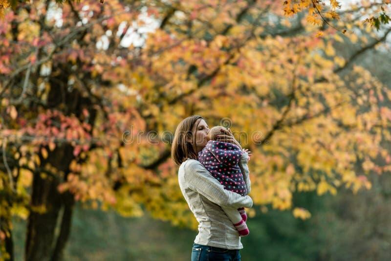Vrouw met baby onder de herfstboom die wordt bevonden royalty-vrije stock afbeelding