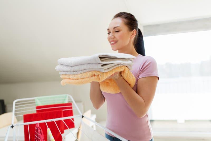 Vrouw met badhanddoeken en drogend rek thuis stock fotografie