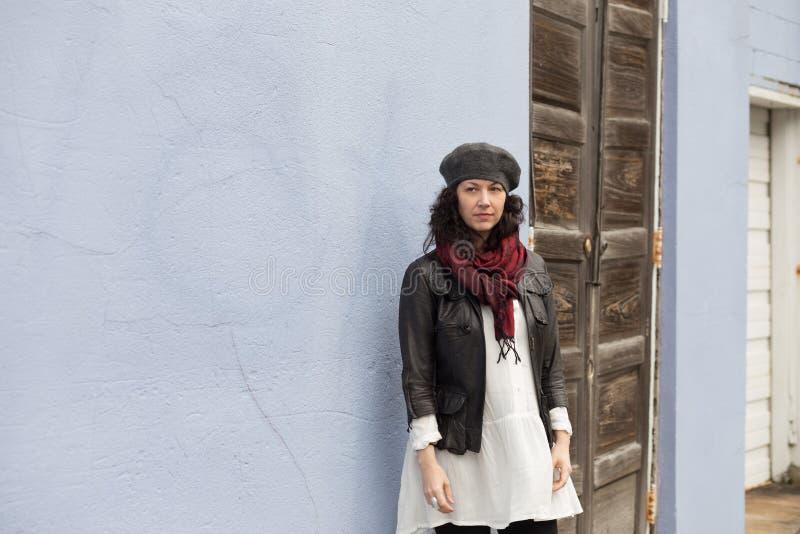 Vrouw met baret die zich tegen de oude bouw bevinden stock afbeelding