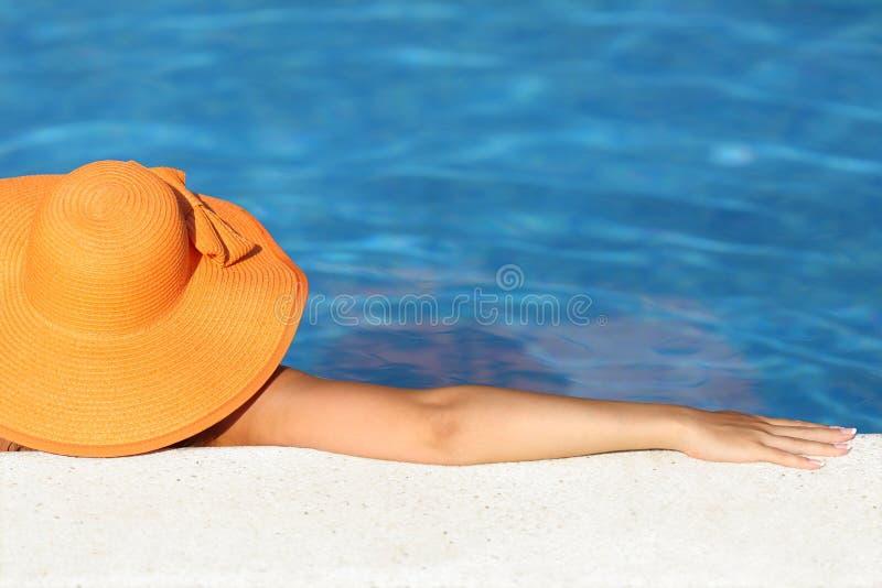 Vrouw met beeldhoed baden ontspannen in een pool die van vakanties geniet stock foto