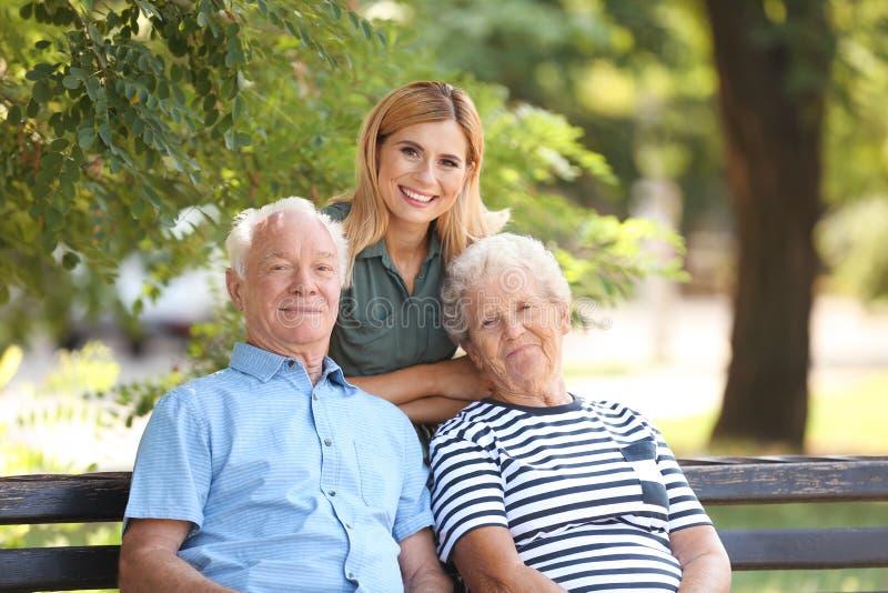 Vrouw met bejaarde ouders in park stock afbeeldingen