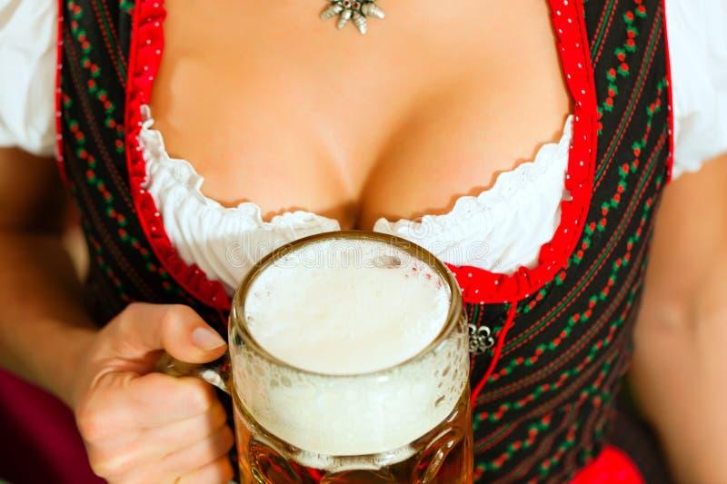 Vrouw met bier op décolleté in Beieren stock afbeelding