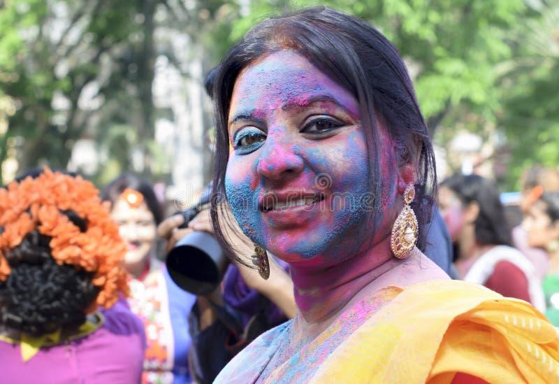 Vrouw met blauwe en roze kleuren wordt gesmeerd die van Holi genieten die stock foto