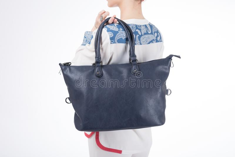 Vrouw met blauwe handtas in handen Geïsoleerde witte achtergrond stock fotografie