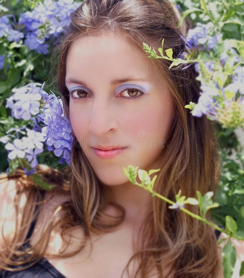 Vrouw met blauwe make-up onder de bloemen royalty-vrije stock foto