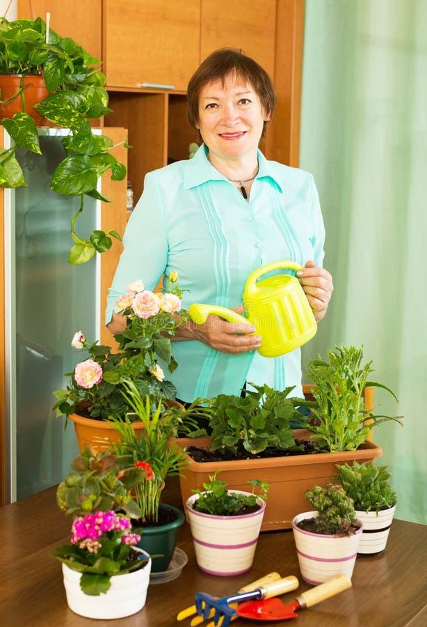 Vrouw met bloemen en gieter royalty-vrije stock fotografie