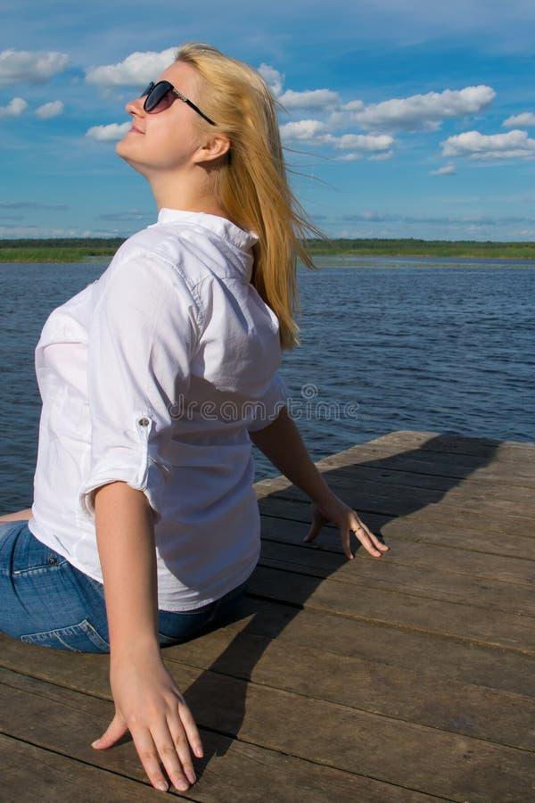 Vrouw met blond haar, op de pijler, tegen het blauwe meer en de hemel, het zonnebaden, close-up stock fotografie