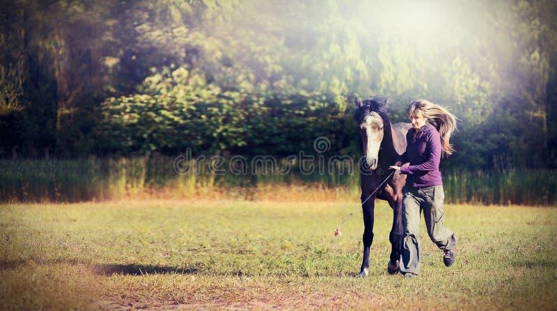 Vrouw met blond lang haar en paard die samen langs mooi gebied over aardachtergrond lopen royalty-vrije stock foto
