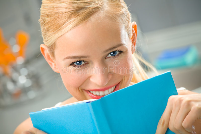 Vrouw met boek bij keuken stock fotografie