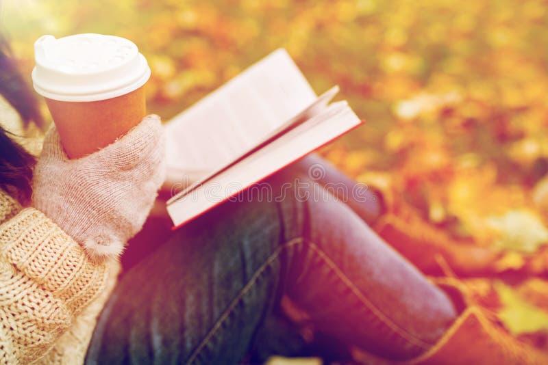 Vrouw met boek het drinken koffie in de herfstpark royalty-vrije stock foto's