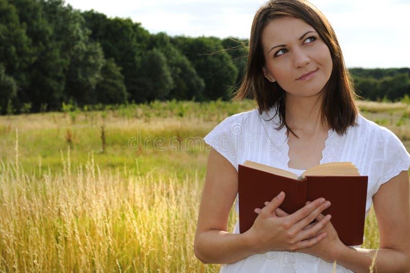 Vrouw met boek op gebied royalty-vrije stock afbeeldingen