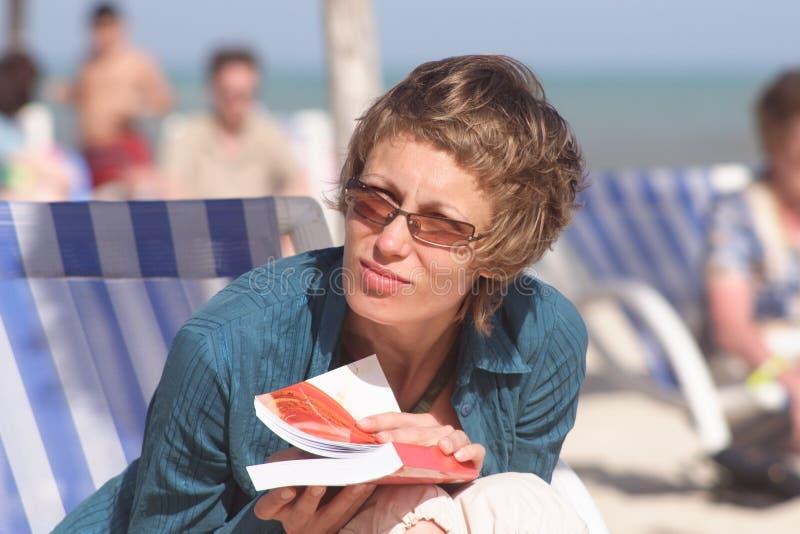 Vrouw met boek op het strand stock fotografie