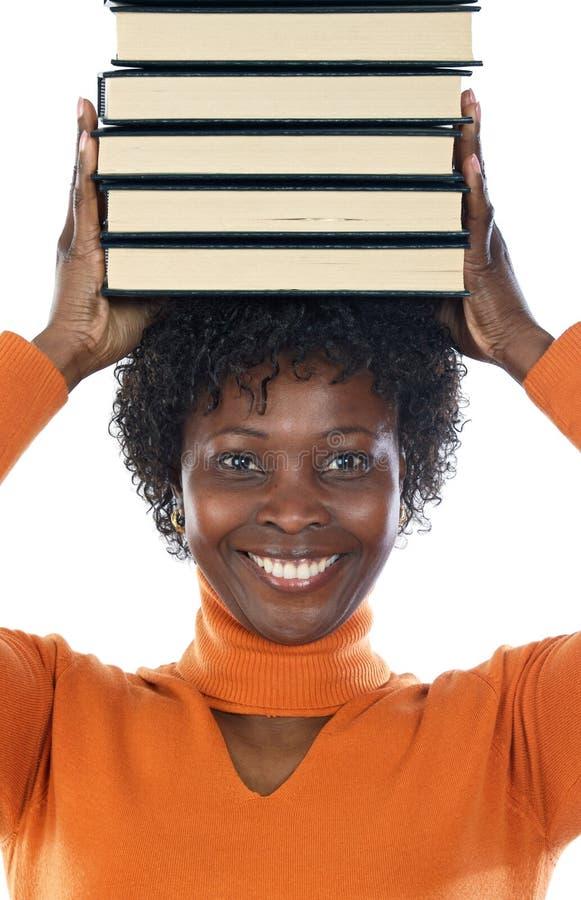 Vrouw met boeken op haar hoofd stock afbeelding