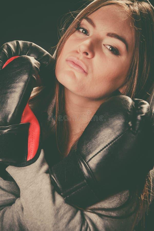 Vrouw met bokshandschoenen gekruiste wapens stock afbeelding