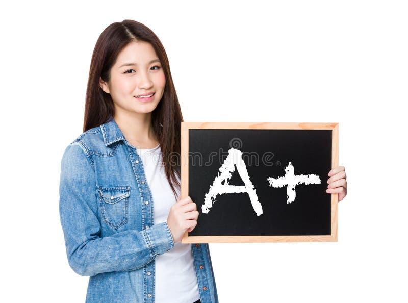 Vrouw met bord die A plus teken tonen stock afbeeldingen