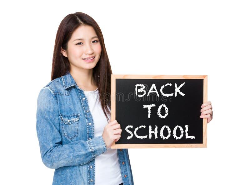 Vrouw met bord die uitdrukking van terug naar school tonen stock foto
