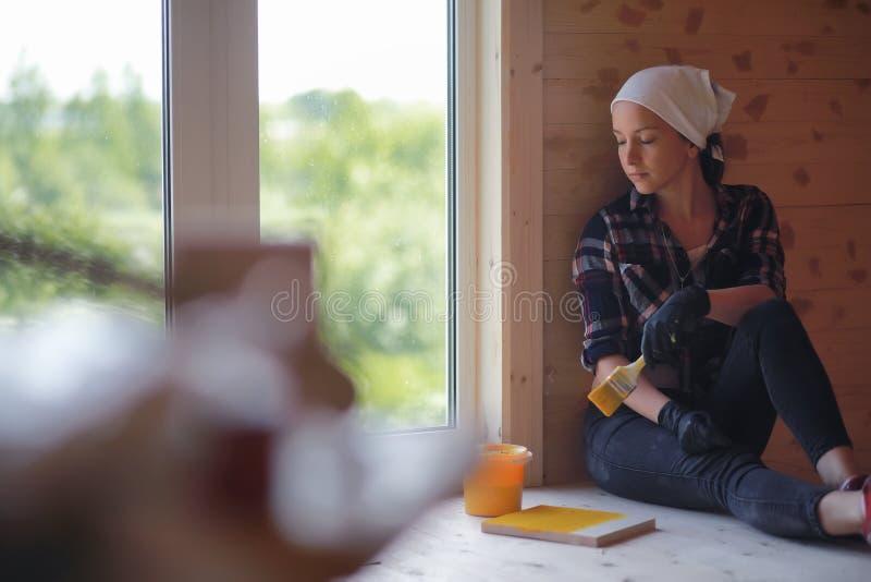 Vrouw met borstelreparatie in een blokhuis stock foto's