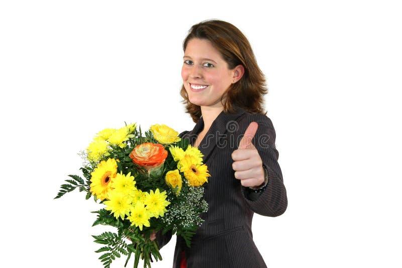 Vrouw met bos van bloemen die met omhoog duimen stellen stock foto