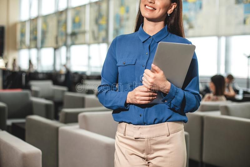 Vrouw met breed glimlach dragend apparaat voor het werk royalty-vrije stock afbeeldingen